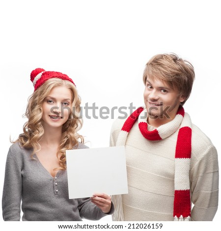 young casual caucasian couple in red scarf and hat holding sign with nice smiles - stock photo