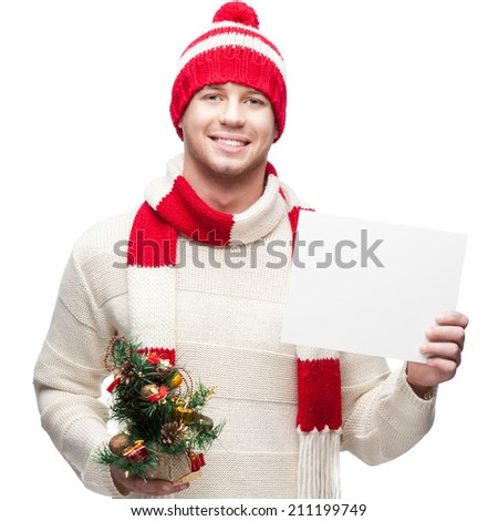 young casual caucasian man in winter hat holding small christmas tree and sign isolated on white background - stock photo