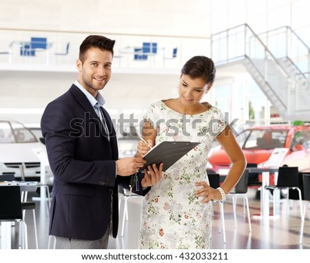 Young casual caucasian woman signing business contract with pen at car dealership saloon indoors. Smiling, standing salesman holding clipboard with documents, looking at camera. - stock photo