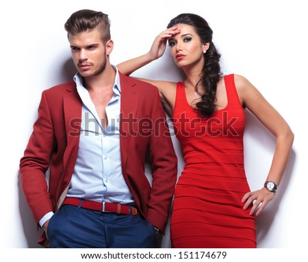 young casual couple against white wall, man looking away and woman looking at the camera