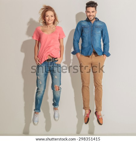 Young casual couple jumping while holding theri hands in pockets. - stock photo