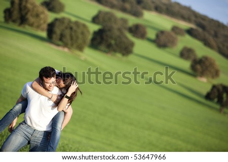 Young casual couple playing on field - stock photo
