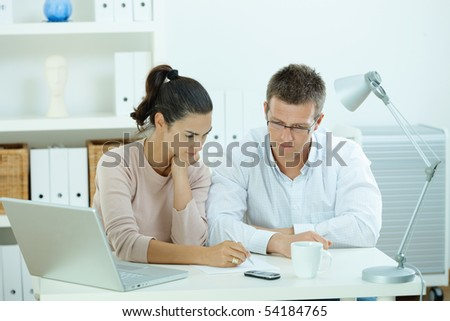 Young casual couple sitting  at desk working together at home office. - stock photo
