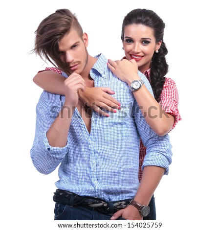 young casual couple with woman holding her hands over man's shoulder and smiling for the camera while he pulls his hair. on white background - stock photo