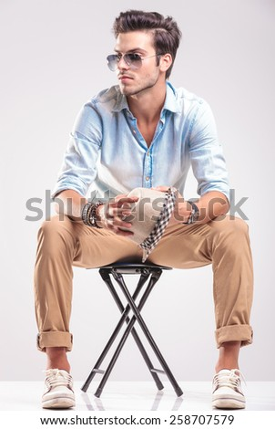 Young casual fashion man looking away while sitting on a stool, holding his hat in his hands. - stock photo