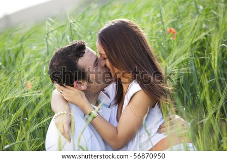 Young casual kissing couple on a wheat field. - stock photo