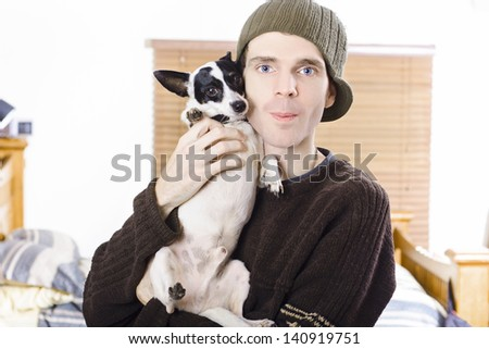 Young casual lifestyle man hugging his cute small dog indoors during winter - stock photo