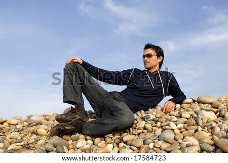 young casual man at the beach stones - stock photo