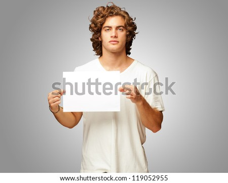 Young Casual Man Holding A Blank Message Isolated On Grey Background - stock photo