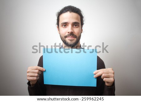 Young casual man holding a blue sign