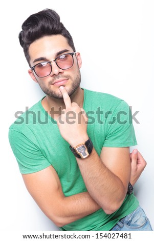 young casual man holding his middle finger on his chin while looking into the camera. on white background