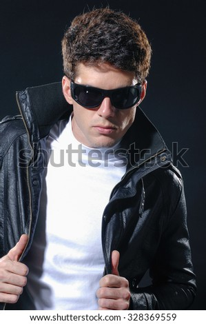 young casual man in sunglasses on a black background - stock photo