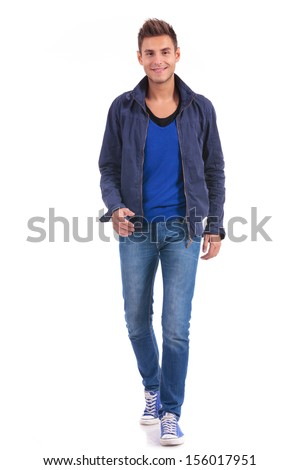 young casual man is walking forward to the camera and smiling