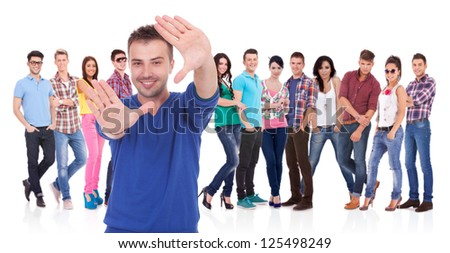 young casual man making a hand frame in front of his team - stock photo
