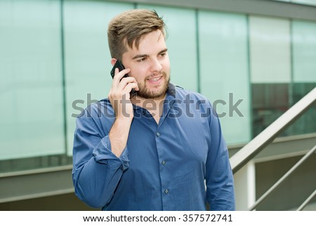 young casual man on the phone inside an office building - stock photo