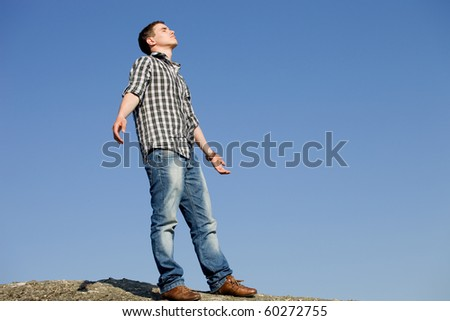 young casual man on top of a rock with the sky as background - stock photo