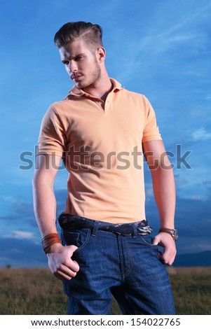 young casual man outdoor looking away from the camera while holding both thumbs in pockets