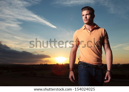young casual man outdoor looking up, away from the camera, with the sunset behind him - stock photo