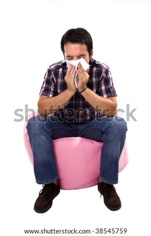Young casual man patient blowing his nouse - stock photo