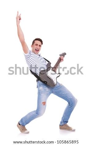 young casual man playing an electric guitar and making a rock and roll hand gesture while screaming - stock photo