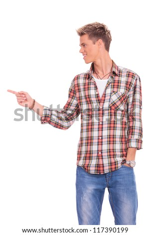 young casual man pointing and looking to his side and holding a hand in his pocket, on white background - stock photo