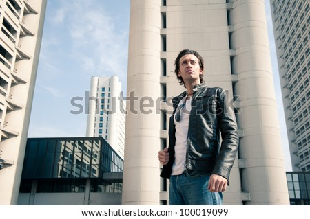 Young casual man portrait with building background.