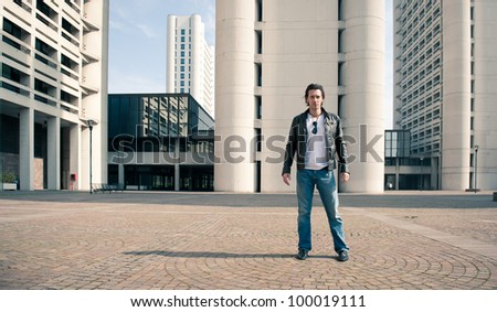 Young casual man portrait with building background. - stock photo