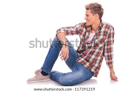 young casual man posing on the floor and smiling while looking to his side, against white background - stock photo