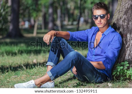 young casual man sitting at the base of the tree, leaning his back on it's trunk and looking at the camera with a serious expression