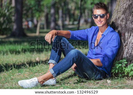 young casual man sitting on the ground and leaning to a tree trunk while smiling at the camera