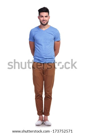 young casual man standing straight with hands at his back on white background - stock photo