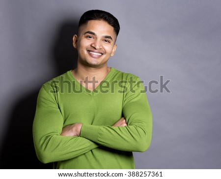 young casual man wearing green on grey background - stock photo