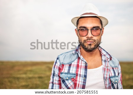 young casual man wearing hat and glasses looking at the camera