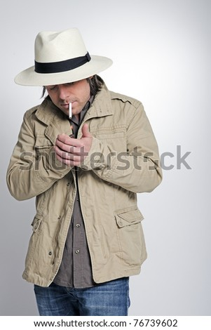 Young casual man with half long hair wearing hat. Western. Cowboy. Gangster. Smoking cigarette.
