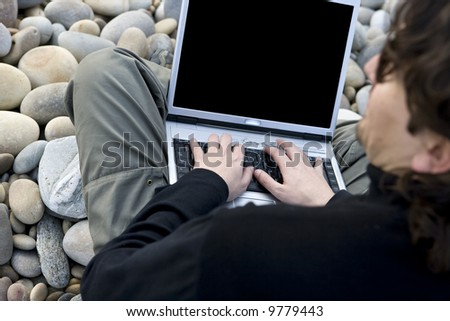 young casual man with laptop computer in the beach - stock photo