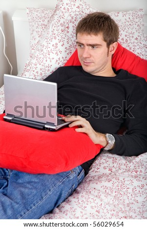 young casual man working with computer in bed - stock photo