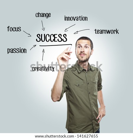 young casual man writing success diagram on glass board with marker - stock photo