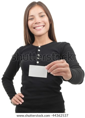 Young casual professional showing blank white business card / paper sign. Beautiful young mixed race chinese / caucasian woman. Isolated on white background. Shallow depth of field, focus on card. - stock photo