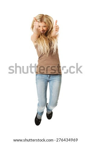 Young casual student jumping showing thumbs up. - stock photo