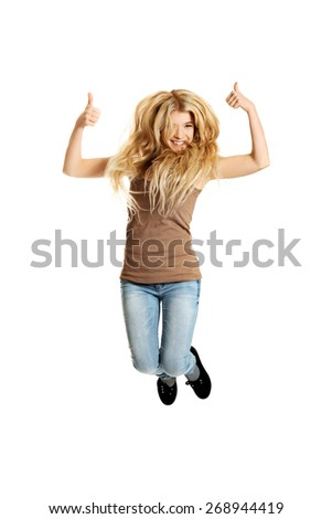 Young casual teenager jumping with thumbs up. - stock photo
