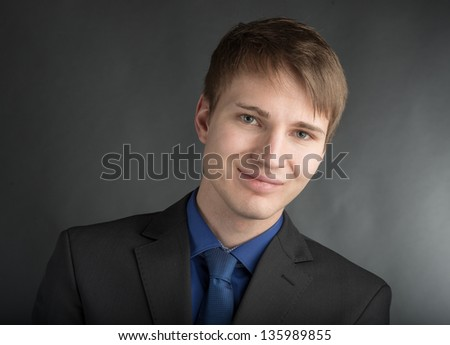 young casual trainee in front of a grey wall - stock photo