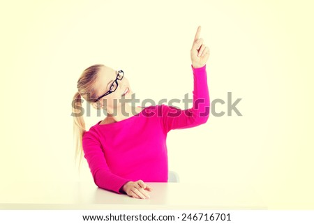 Young casual woman by a desk pointing aside.  - stock photo