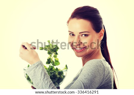 Young casual woman eating lamb's lettuce - stock photo