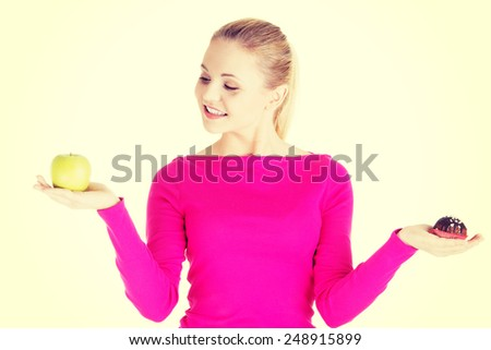Young casual woman holding an apple and cookie.  - stock photo