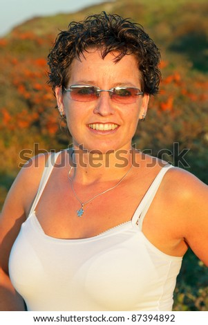 Young casual woman wearing sunglasses enjoying outdoor in dune landscape on clear sunny day with blue sky - stock photo
