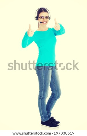 Young casual woman with headphones and microphone showing ok. - stock photo