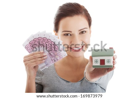Young casual woman with money and house. Isolated on white. - stock photo
