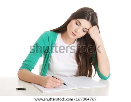 Young casual woman writing in workbook. Isolated on white. - stock photo