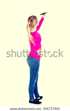 Young casual woman writing on copy space. Back view.  - stock photo