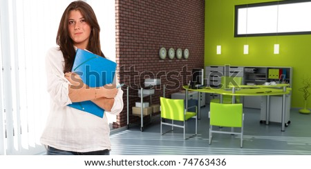 Young casually dressed woman  carrying a folder in an office interior - stock photo